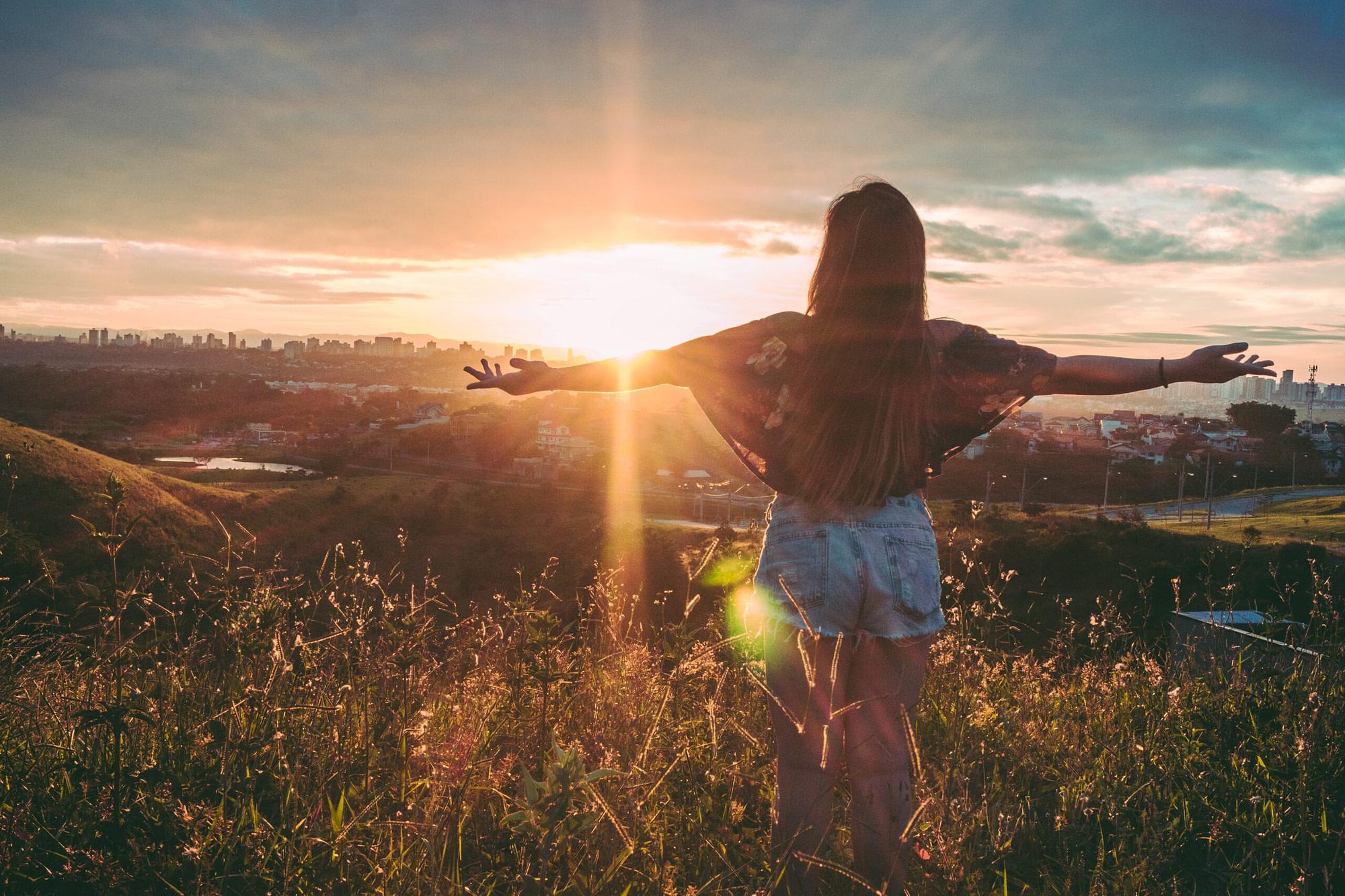 omdenken Van uitdaging naar kans – Deel 2: Omdenken & focus op een ander perspectief woman stands on mountain over field under cloudy sky at 847483 scaled